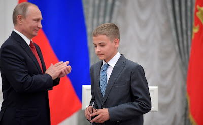 Russian President presents passports to young citizens of Russia.