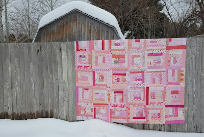 pink log cabin quilt on fence