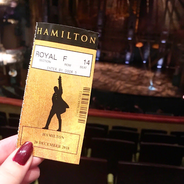 Hamilton seat ticket held up from dress circle, view of the stage in the background