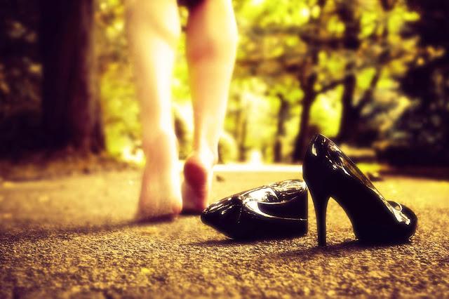 Pies descalzos de mujer caminando, tras sus zapatos de tacón abandonados sobre el suelo