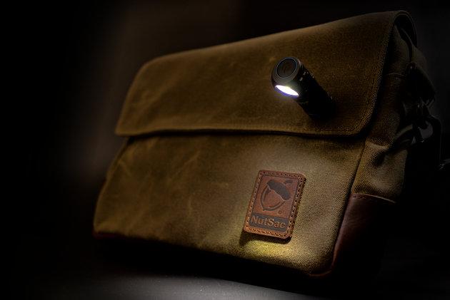 Torba NutSac model Mag-Satch z przyczepioną do magnesu w torbie latarką Olight H1 Nova