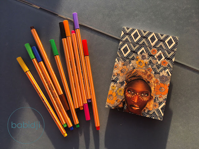 Carnet de note avec le portrait d'une africaine sur la couverture et des stylos stabilo