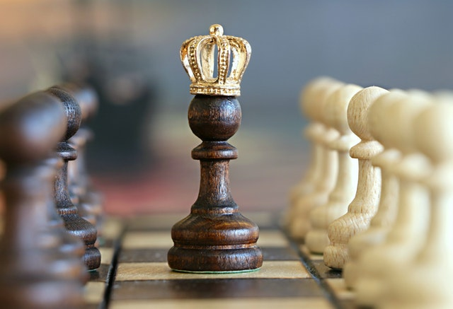 Chess piece with a gold crown on top surrounded by two opposing parties