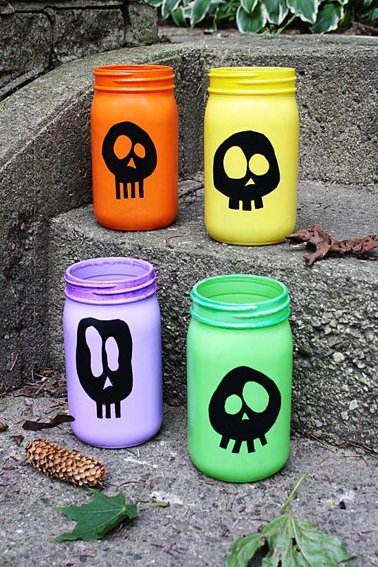 Colorful skull luminaries for Halloween. 25 best Halloween Mason jar craft ideas. Mason jar painted ghost ideas. Scary ghost paint on Mason jar. Halloween ghost decoration on Mason jar ideas. Best Halloween jar decoration for outdoor. Halloween party decoration ideas.