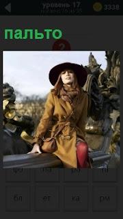 Девушка сидит на перилах и демонстрирует свое красивое пальто