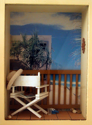 Modern one-twelfth scale miniature balcony near the sea, with a director's chair  and sunhat.