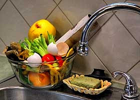 A small glass bowl filled with kitchen scraps sitting next to a soap dish on a stainless steel sink.