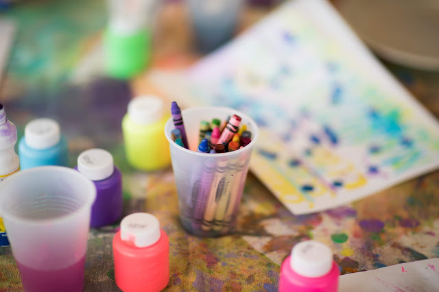 Table showing a pot of paints, crayons and paintings