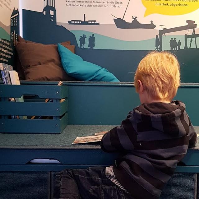 5 Ausflüge mit Kindern in Kiel bei Regenwetter. Bei Schlechtwetter machen die Kinder es sich in der Bücherecke des Schifffahrtsmuseums Kiel gemütlich.