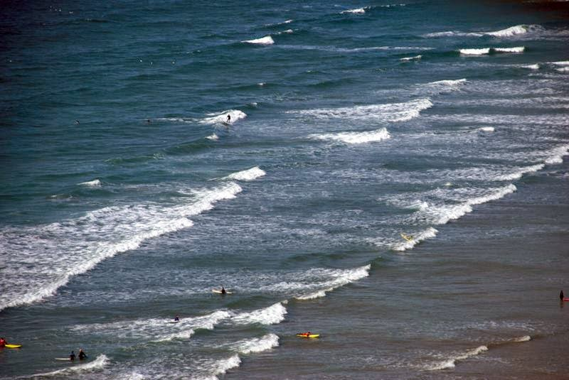 Surfers on the beach at Mawgan Porth in North Cornwall.