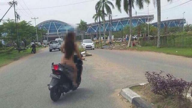 Aksi seorang perempuan yang nekat mengendarai sepeda motor tanpa busana