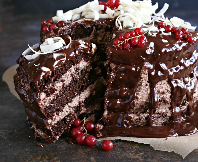 Recipe for a 4 layer chocolate cake with raspberry syrup, chocolate mousse filling and ganache topping.