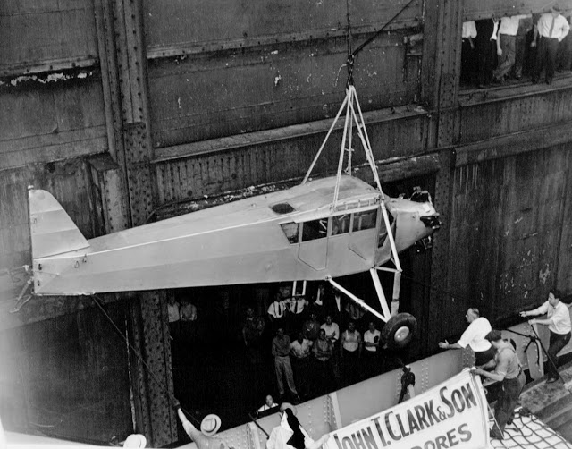 Douglas Corrigan's 'rattletrap' plane returning to NYC via ship. The aircraft, without wings, being lowered from the ship. A crowd of workmen and sailors watch the event. 1938. Wrong Way and other stories of pilots. marchmatron.com