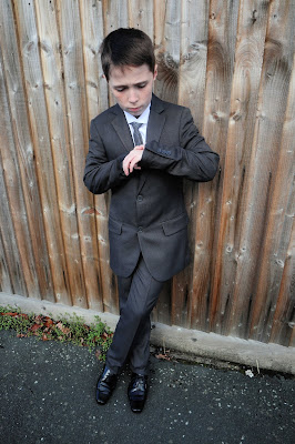 Boy leaning against a fence, looking at his watch, in a grey Roco suit.