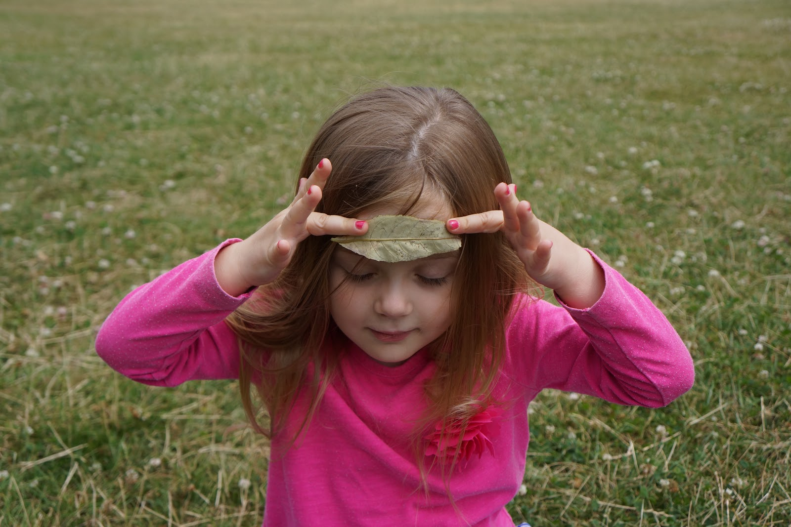 girl holding a leaf on her forehead