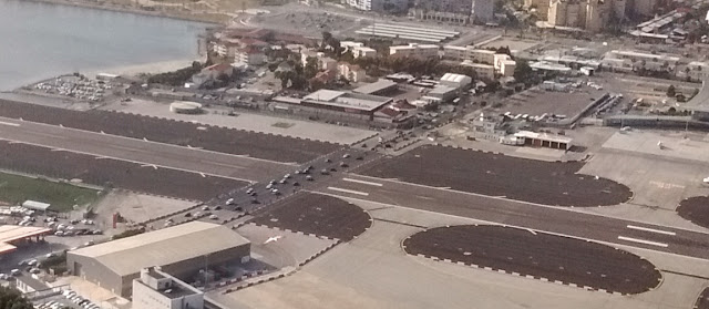 Photo of cars and other traffic crossing the runway of the Gibraltar airport after having waited for a plane to land. The road crossing the runway is the only land route in or out of the British territory which borders Spain.