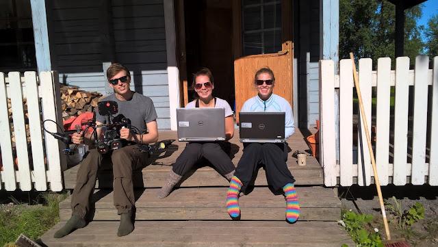 Kolme henkeä istuu auringossa rappusilla, kahdella läppäri sylissä, yhdellä vedenalaiskamera