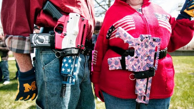 Open carry. Man and wife with large firearms wrapped in red white and blue American flags.Snark on the 4th and other stories about Merica. marchmatron.com