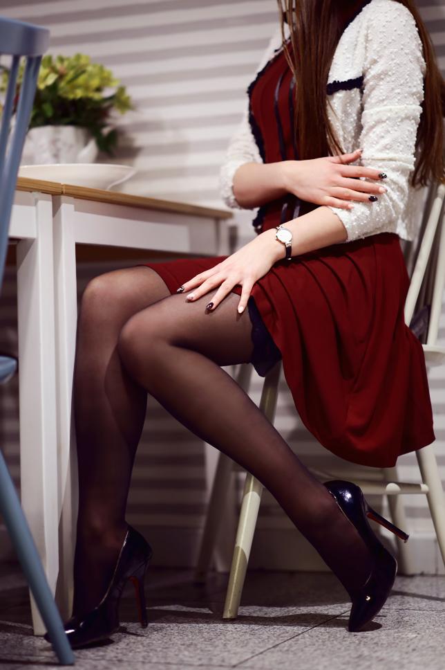 Czerwona sukienka, biały żakiet, czarne pończochy i lakierowane szpilki