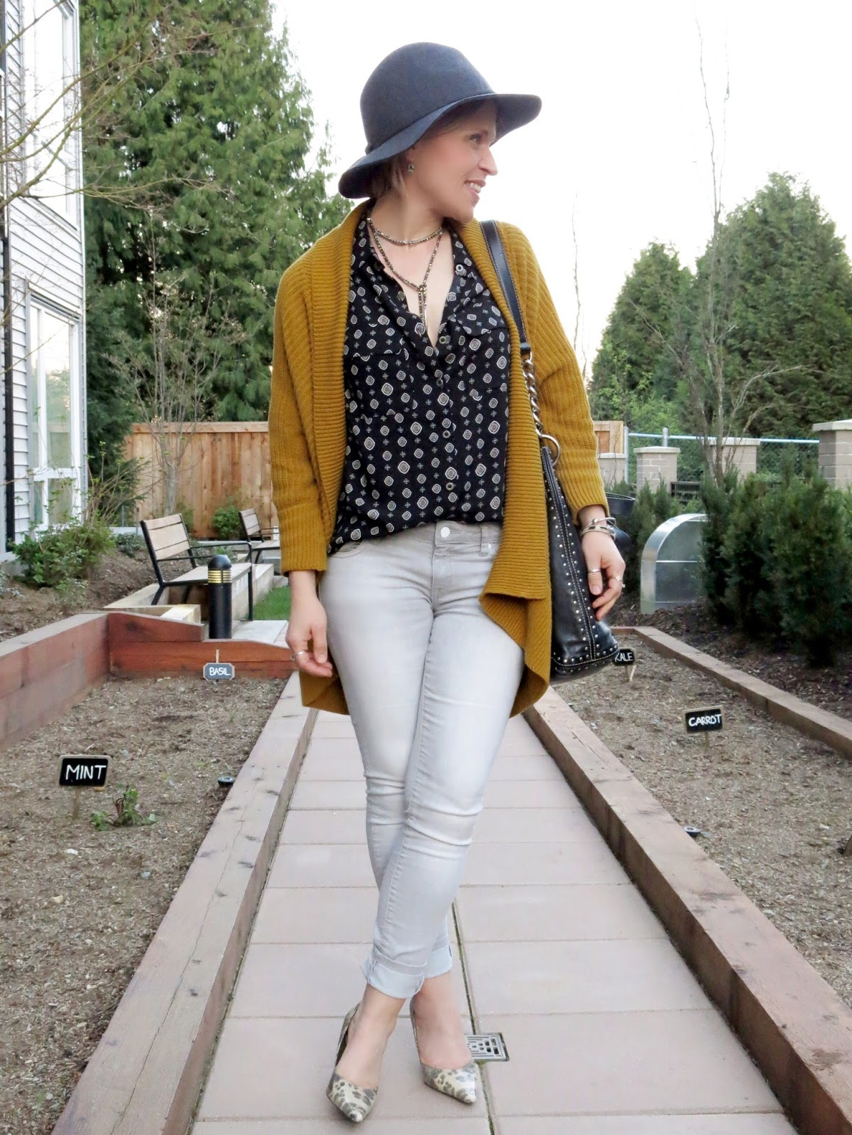 styling a black patterned shirt with grey skinnies, reptile pumps, a drapey mustard cardigan, and a floppy hat