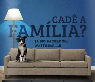 Foto de um sofá marrom claro de três lugares, sentado na primeira almofada à esquerda, um cão da raça border collie, sozinho. Próximo à parede azul atrás do sofá, uma luminária alta, com cúpula branca, ilumina as letras enormes pretas e lê-se: Cadê a Família? E abaixo, em letras menores: Ta no Facebook, Wattssap....!!