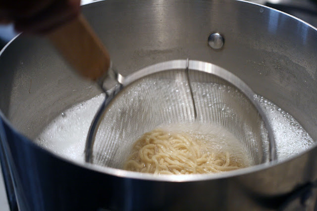 A wire mesh strainer containing the noodles in a pot of hot water.