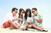 four people on beach looking at ipad