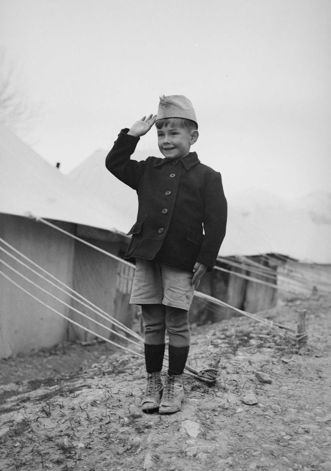 A young Polish refugee does a military salute outside his tent.