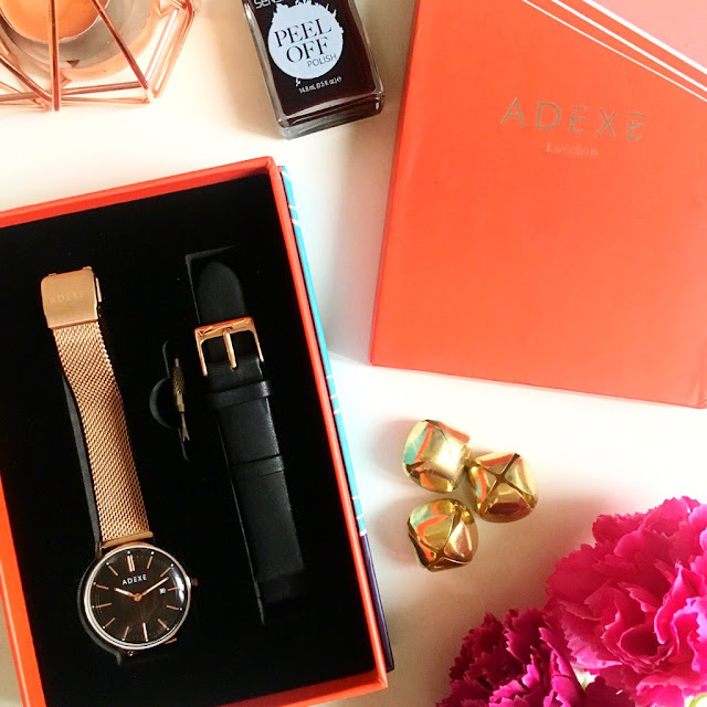 flatlay - watch in its box on the left side, box lid on the right side, flowers and gold accessories in the spaces