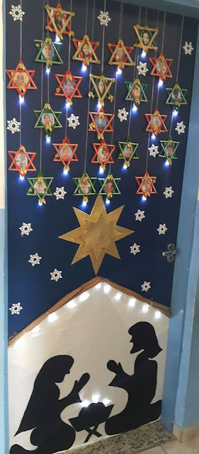Linda porta decorada com presépio em silhueta e porta retratos em formato de estrelas.