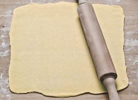 Masa básica  para pastas caseras, estirada con un palote de amasar encima.