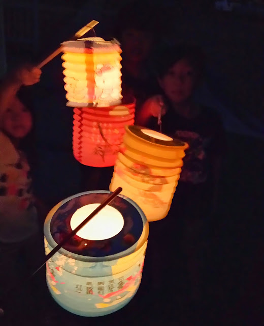 celecrating mid-autumn festival with lit lanterns and moon cakes.
