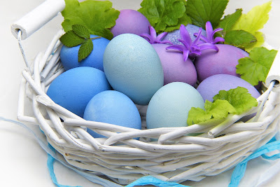 pastel colored Easter eggs in a white basket with blue ribbon