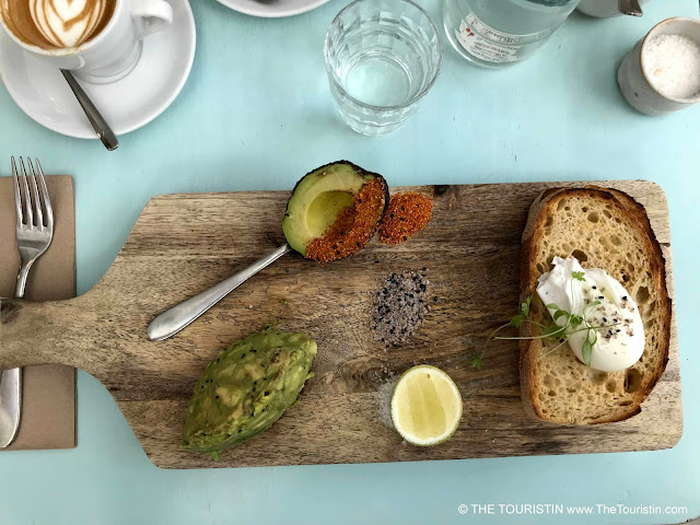 Flat white espresso drink, two pieces of avocado, sourdough bread with a poached egg and a slice of lemon on a wooden board.