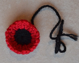 A rounded 'mini poppy' with a black centre and cupped red stitches to represent petals. A black thread is still attached.