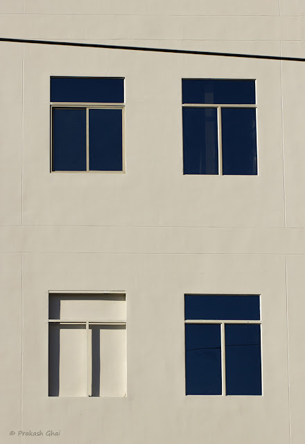 A Minimalist Photo containing Four Windows out of which one unfinished window stands out as the odd one.