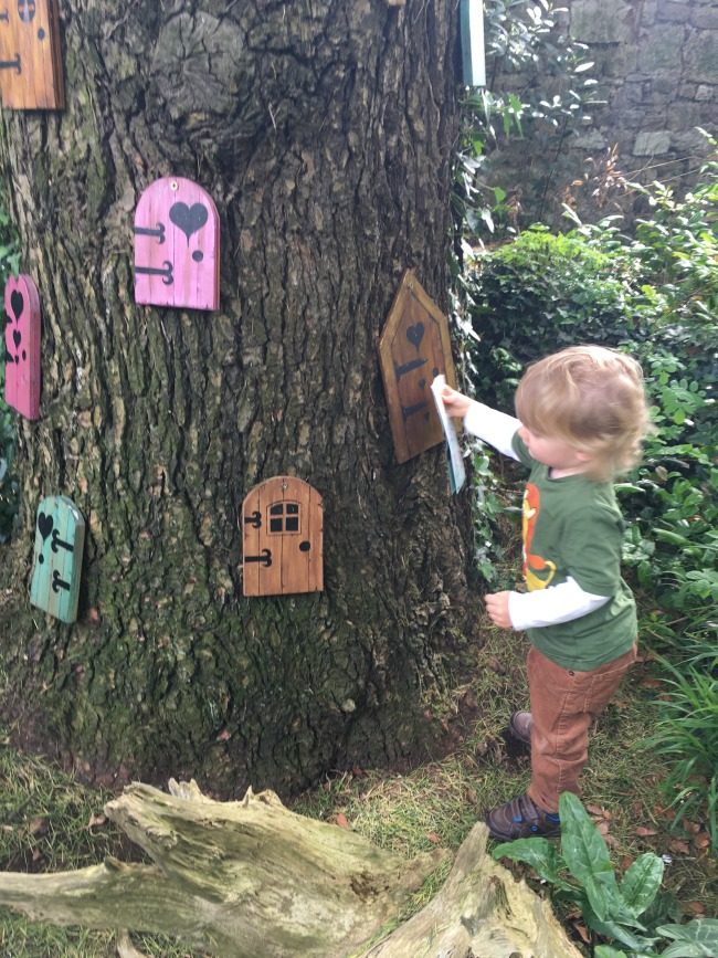 toddler-touching-fairy-doors-on-a-tree