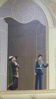 Azethot und Zazamael stehen auf einem Balkon vor einer großen geöffneten Tür in militärischer Pracht. Zazamael hat einen iPod an.
