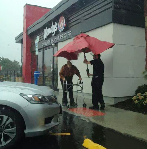 Wendy's employee removes umbrella from table to protect elderly man from rain.