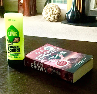 A rectangular clear plastic bottle filled with green liquid with a picture of a Lime with Original Source in big bold black font with Lime in white font next to a rectangular book saying dan brown in white font on a brown rectangular table  on a bright background