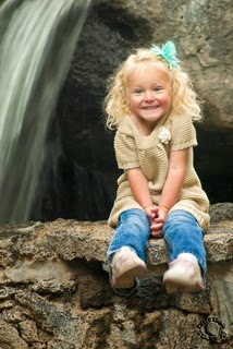 Professional portrait of a girl sitting on a rock by a waterfall professionally photographed by Cramer Imaging in Idaho Falls, Bonneville, Idaho
