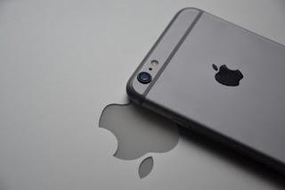 صور بها آيفون عليه لوجو التفاحة وتحته ورقة عليه شعار آبل مقلوب