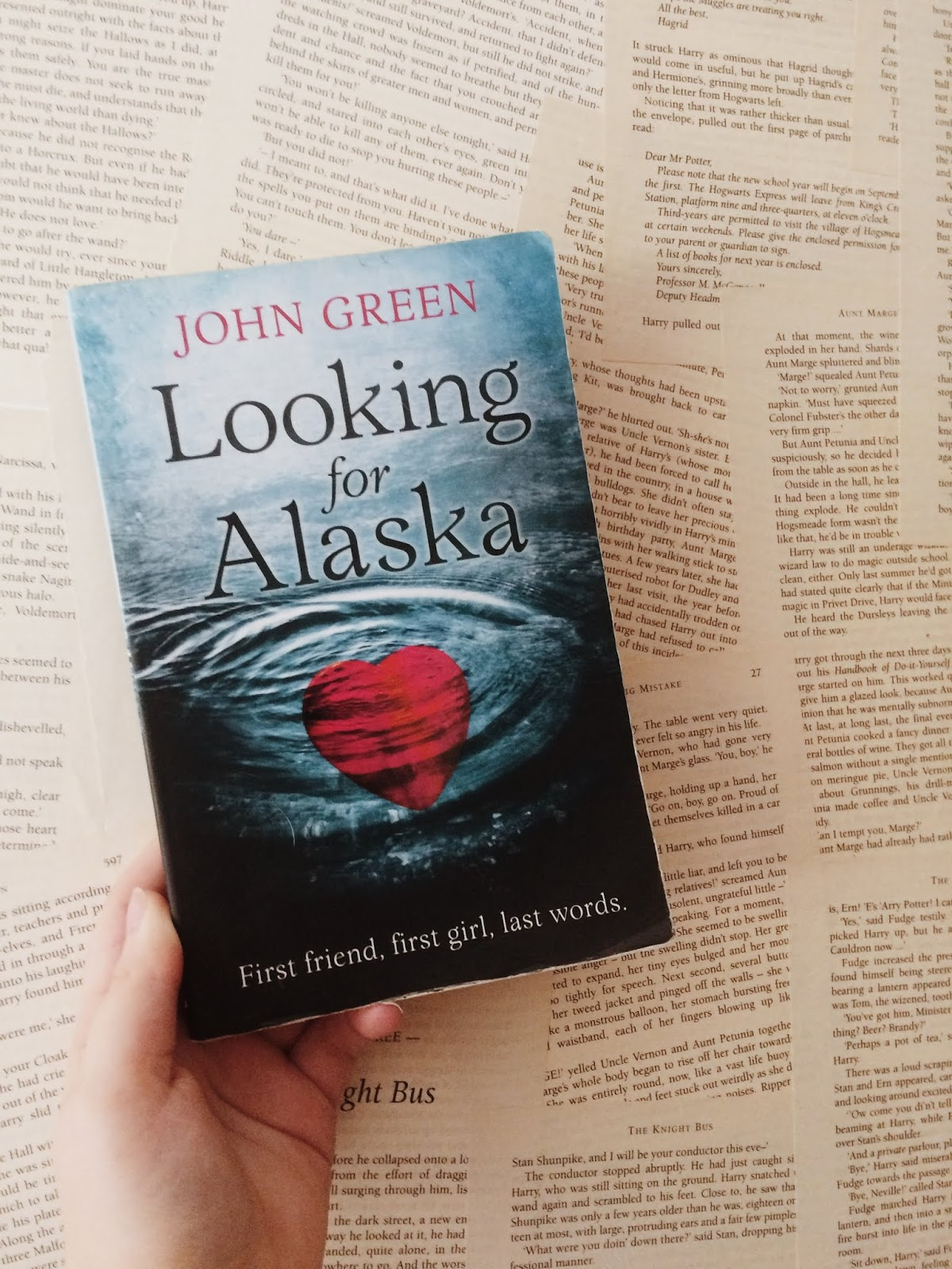 Photo of the book Looking for Alaska by John Green, held up over a background of loose pages from book
