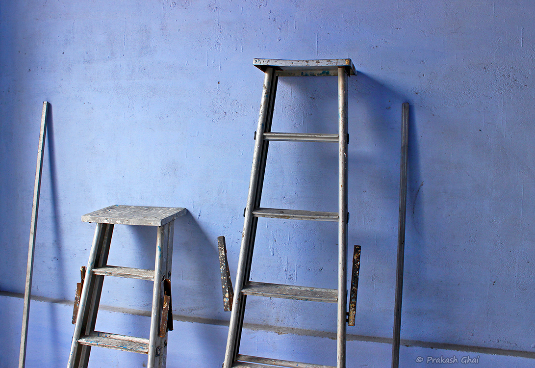 A Minimalist Photo of Metal Ladders at Diggi Palace Jaipur Literature Art Festival, against a blue wall.