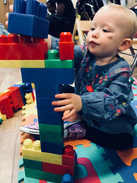 A toddler building a not very stable tower with Mega Blocks