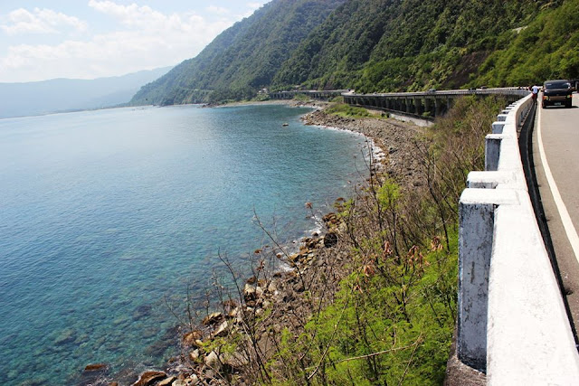 A view of the highway adjacent to the rocky shoreline and a view of the clear sea waters.