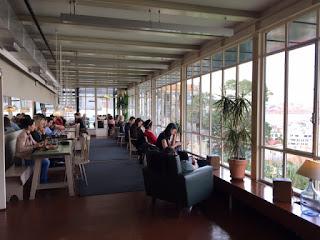 espaço do café com mesas, cadeiras e pessoas e uma vista linda de Lisboa