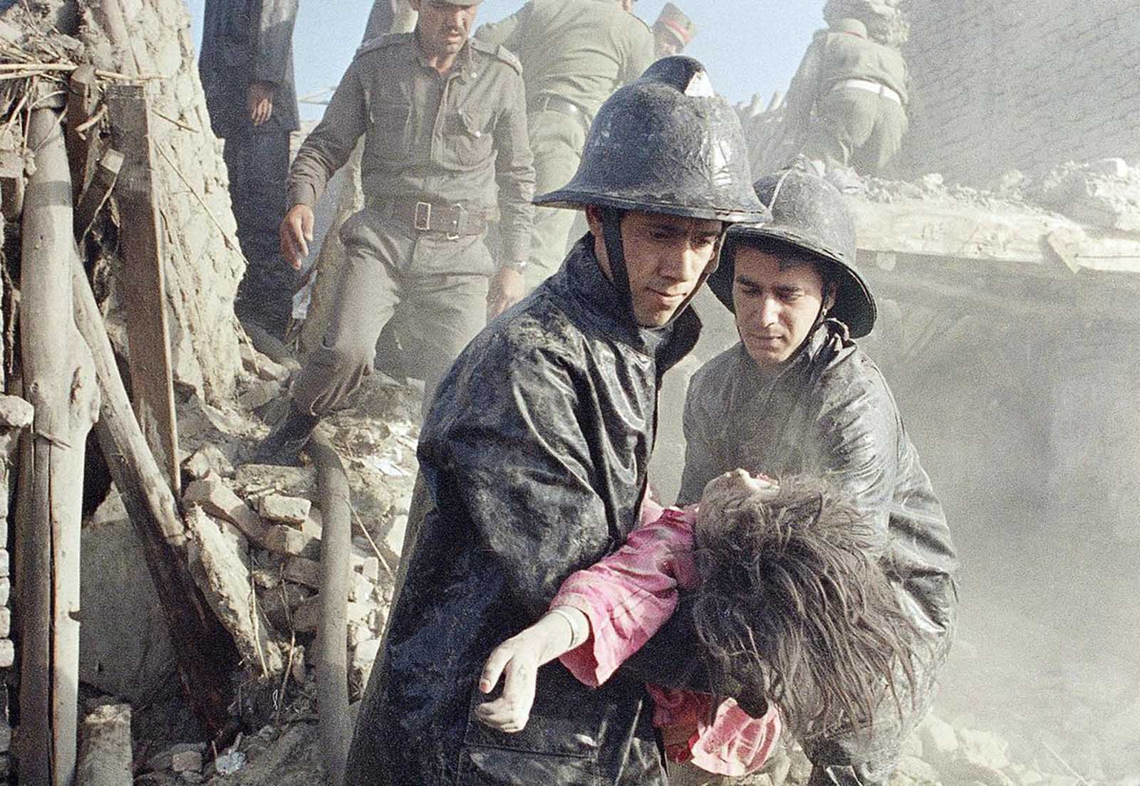 Afghan firefighters carry the body of a young girl killed in a powerful bomb blast that shattered rows of homes and shops in downtown Kabul on May 14, 1988. At least eight people were killed and more than 20 injured by the explosion, believed to be planted in a truck on the eve of the Soviet withdrawal from Afghanistan.