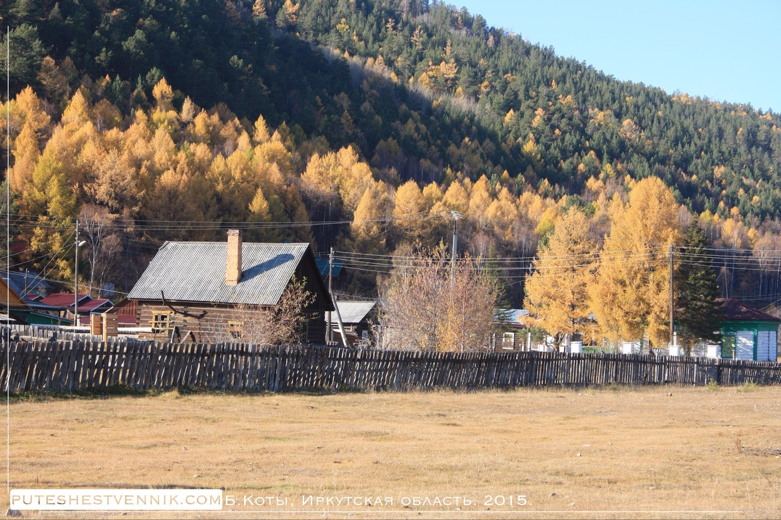 Забор, деревня и склон горы с лесом