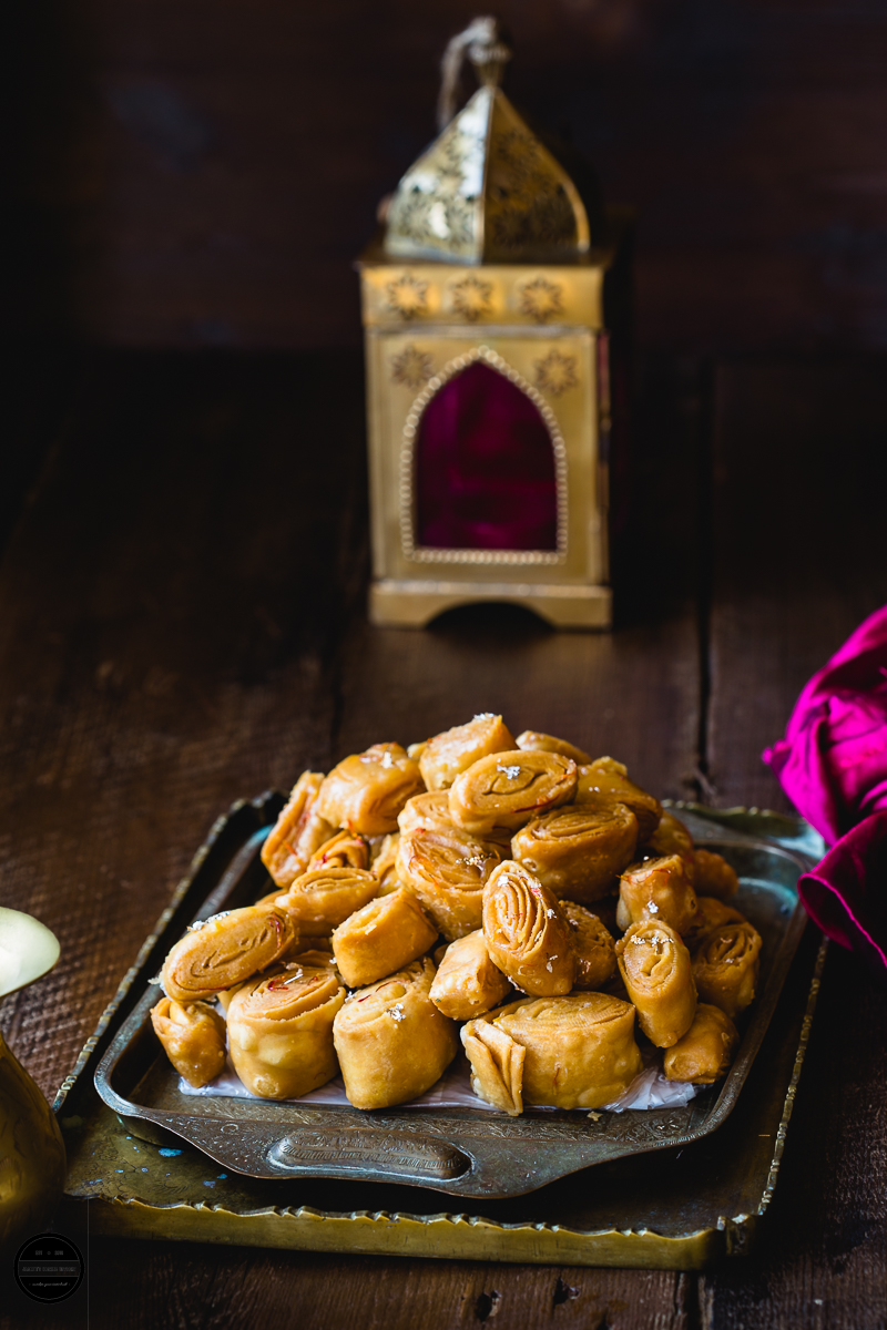 Kesar Khaja is a sweet layered pastry that is soaked in a sugar syrup